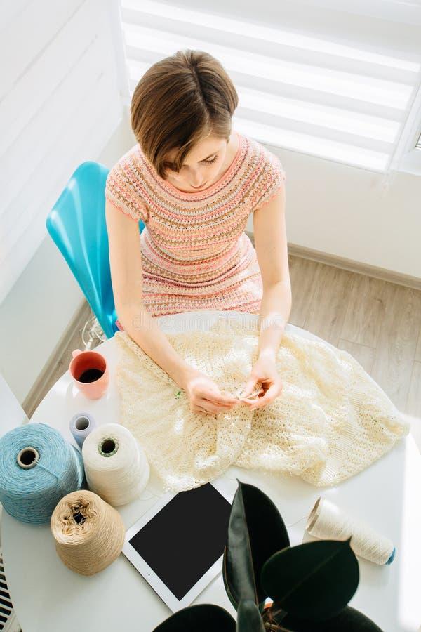 Взгляд сверху craftswoman вязать что-то с вязанием крючком в уютном рабочем месте дома внутреннем Женская работа с нежным шнурком стоковая фотография