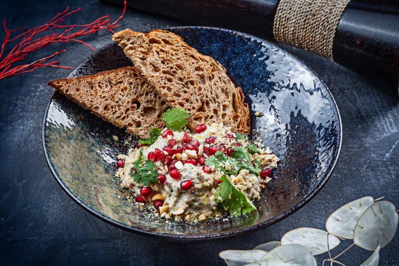 Взгляд сверху ghanoush Бабы в темной плите Традиционная арабская еда Закуска помятого сваренного баклажана смешанного с tahini r стоковые изображения