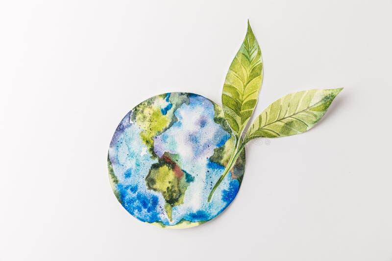 взгляд сверху handmade красочного бумажного глобуса при листья зеленого цвета изолированные на сером цвете, защите среды и концеп стоковое фото rf