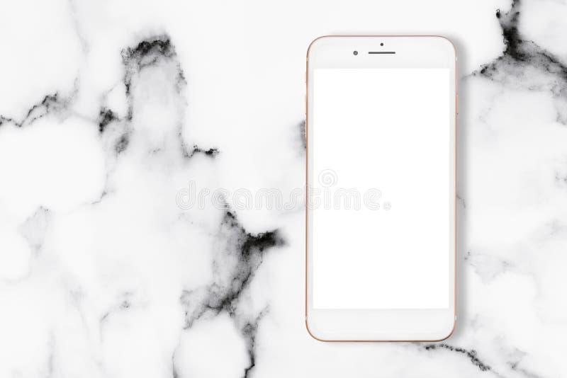 Взгляд сверху smartphone на белой мраморной таблице