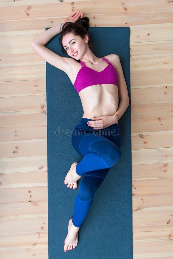 Взгляд сверху sportswear довольно тощей молодой кавказской женщины нося лежа на циновке ослабляя после разминки в спортзале стоковая фотография rf