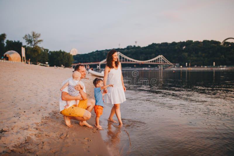 Взгляд семьи с 2 детьми малыша Outdoors рекой летом Счастливая молодая семья имеет потеху на пляже на заходе солнца стоковые изображения