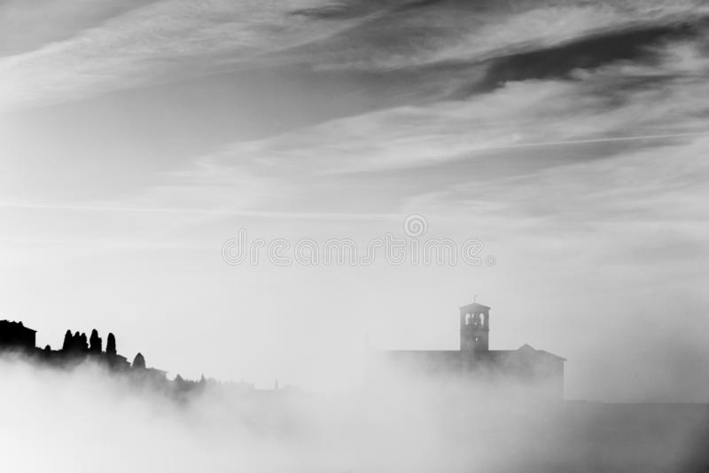 Взгляд силуэта церков StFrancis в Assisi в середине тумана под глубоким небом с облаками стоковые фото