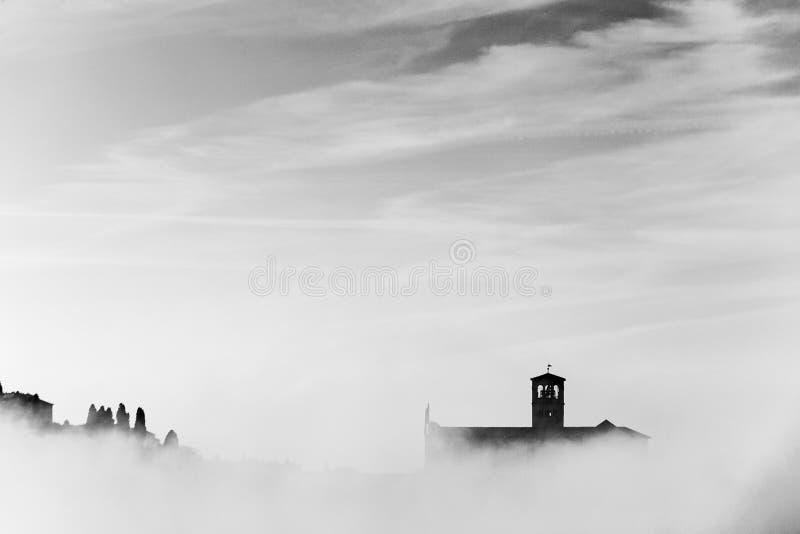 Взгляд силуэта церков StFrancis в Assisi в середине тумана под глубоким небом с облаками стоковое фото