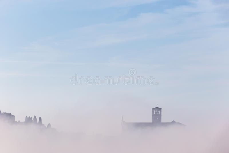 Взгляд силуэта церков StFrancis в Assisi в середине тумана под голубым небом с облаками стоковые фото