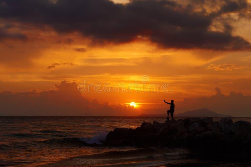 Взгляд силуэта человека стоя на пляже камня моря и снимая selfie с красивым изумительным заходом солнца оранжевых красных цветов  стоковое изображение rf