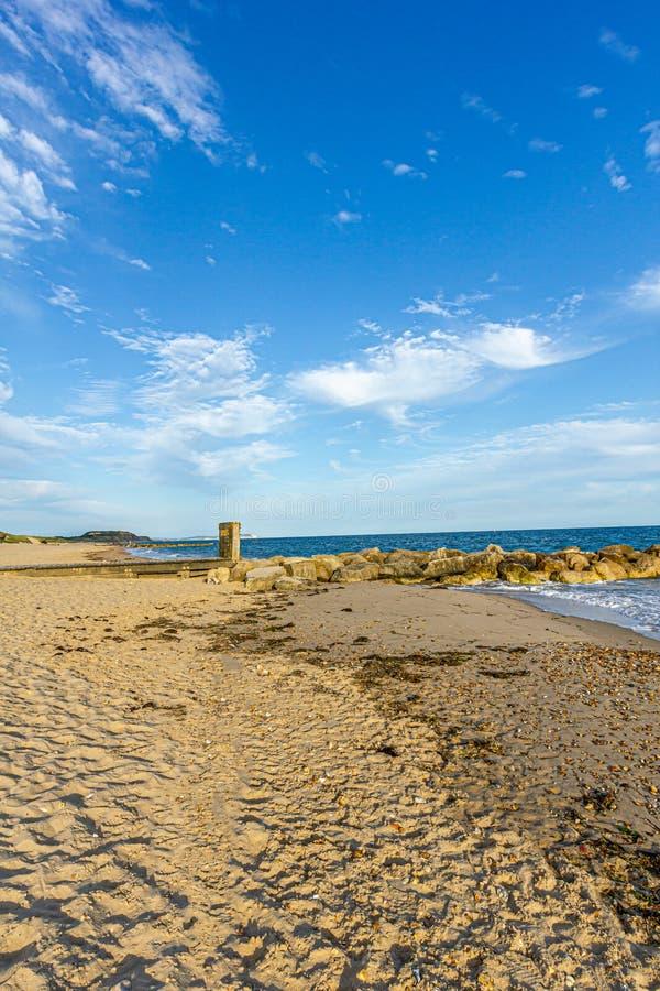 Взгляд скалистого волнореза groyne вдоль песчаного пляжа, изменчивого открытого моря и разбивая волны под величественным голубым  стоковая фотография