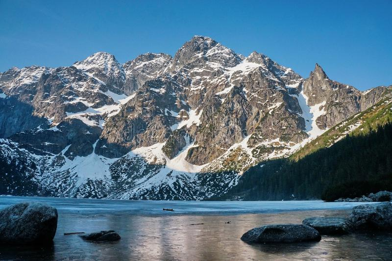 взгляд снега покрыл горные пики над водой озера, Morskie Oko, глазом моря, соотечественником Tatra стоковое фото