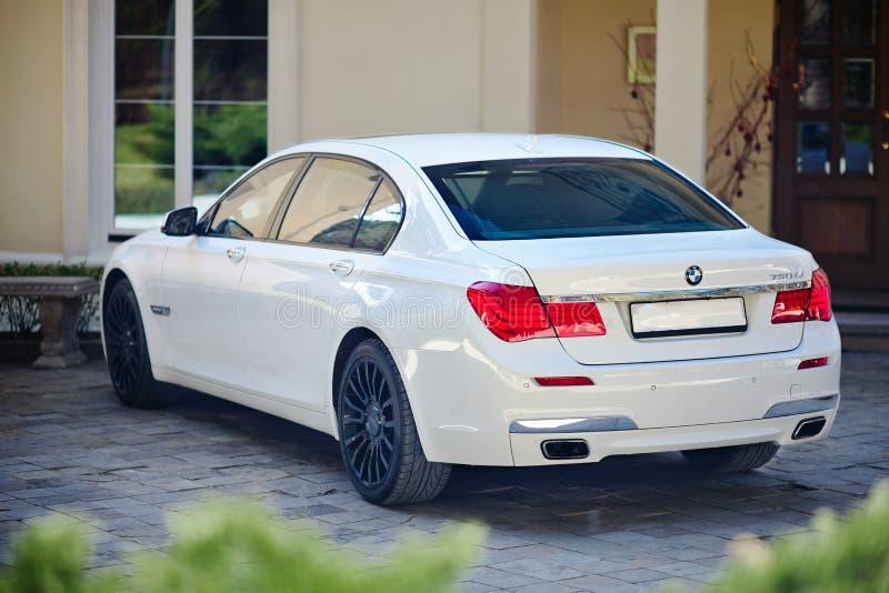 Взгляд современного роскошного автомобиля BMW 750Li XDrive трехчетвертной верхний припаркованный на каменной вымощенной стоянке о стоковое изображение
