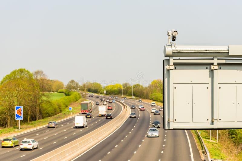Взгляд солнечного дня движения шоссе Великобритании с камерой CCTV на переднем плане стоковые изображения rf