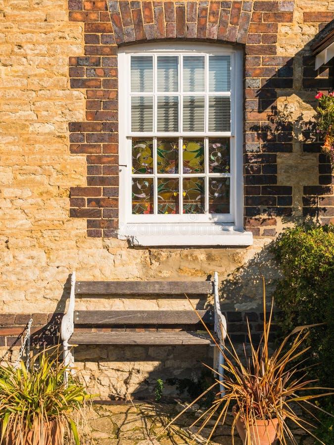 Взгляд солнечного дня старого белого окна на старой кирпичной стене и стенда в Англии стоковые изображения rf
