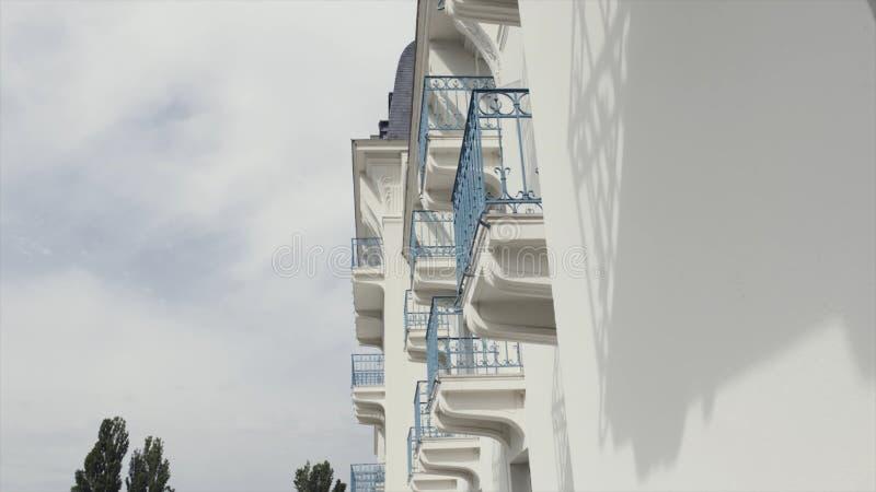 Взгляд со стороны балконов с голубыми чугунными перилами современного здания, архитектурноакустической предпосылки E Белая стена стоковое фото rf