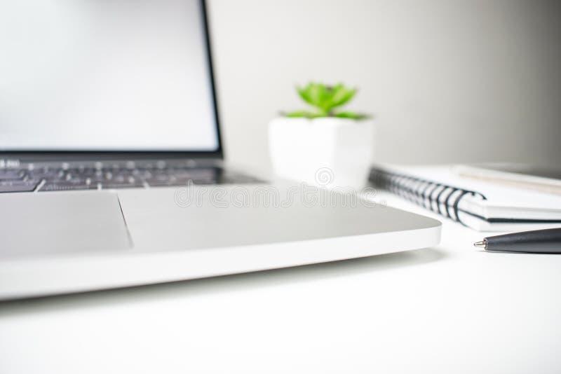 Взгляд со стороны, белый стол с ноутбуком, тетрадь и ручка Взгляд сверху с зоной экземпляра стоковое фото rf