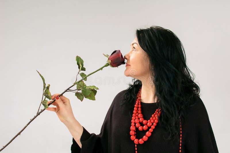 Взгляд со стороны добавочной модели размера в черном платье и этнической красной розе обнюхивать ожерелья на серой предпосылке в  стоковое фото rf