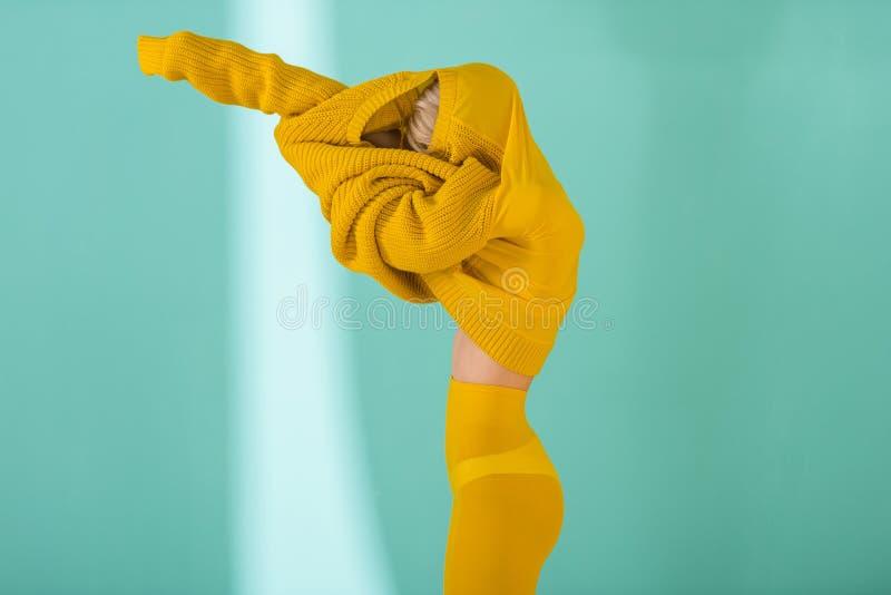 взгляд со стороны женщины в желтых колготках нося желтый представлять свитера стоковое изображение rf