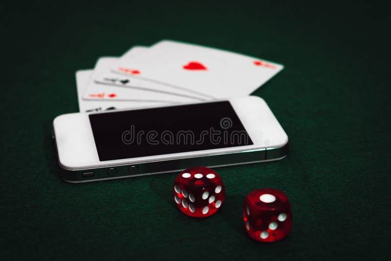 Взгляд со стороны зеленой таблицы покера со смартфоном, чешет и dices Играя в азартные игры онлайн наркомания приложения стоковое фото