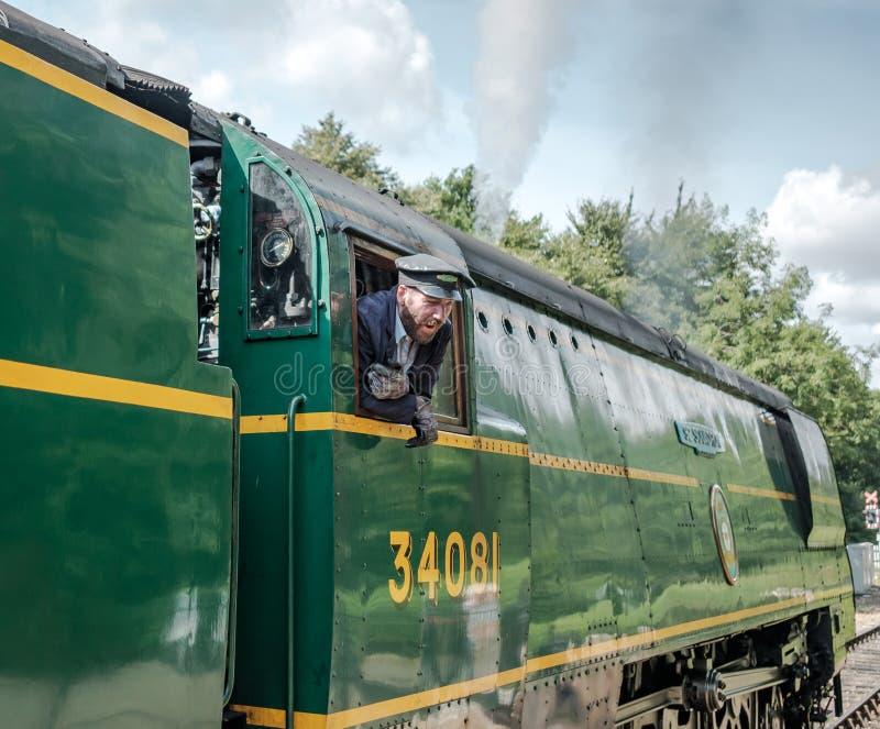 Взгляд со стороны известного великобританского локомотива пара, увиденный с ее водителями по мере того как она около высаживаться стоковые фото
