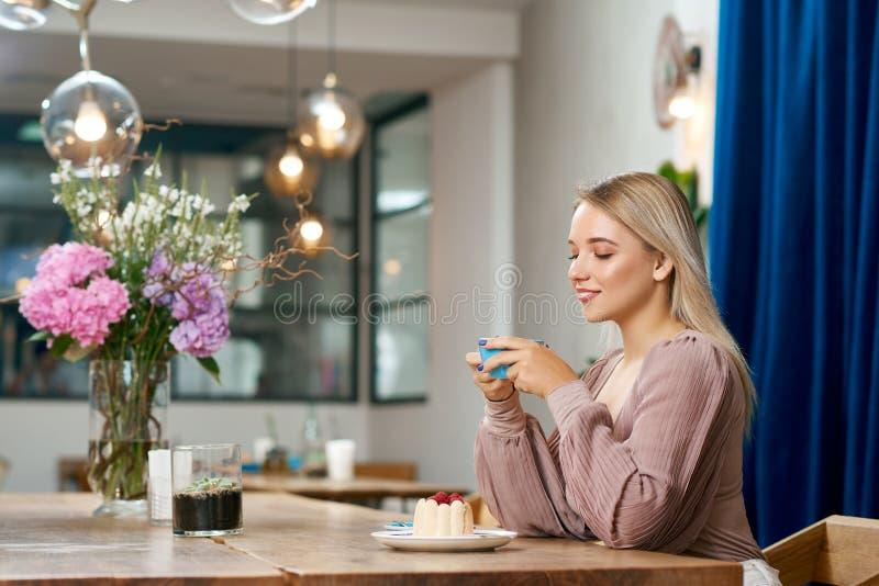 Взгляд со стороны кофе милой девушки выпивая в местном кафе с стильным интерьером стоковая фотография rf