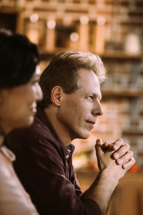 взгляд со стороны красивого задумчивого зрелого человека стоковая фотография