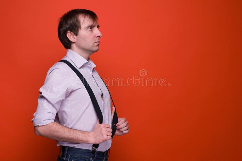 Взгляд со стороны красивого уверенного человека в розовой рубашке с руками на черном подтяжк смотря прочь и думая стоковые изображения