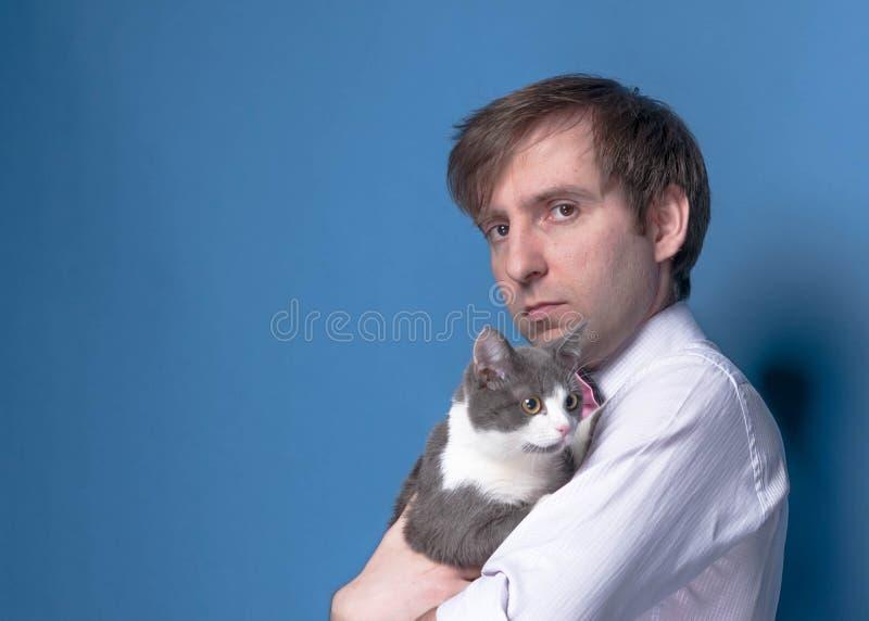 Взгляд со стороны красивого человека в розовой рубашке смотря камеру и держа прелестного серого кота стоковая фотография rf