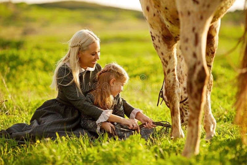 Взгляд со стороны молодой матери с маленькой девочкой в платьях обнимая пятнистую лошадь на зеленом луге стоковое фото rf