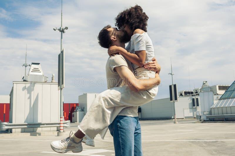 взгляд со стороны молодых многонациональных пар обнимая и целуя стоковое фото