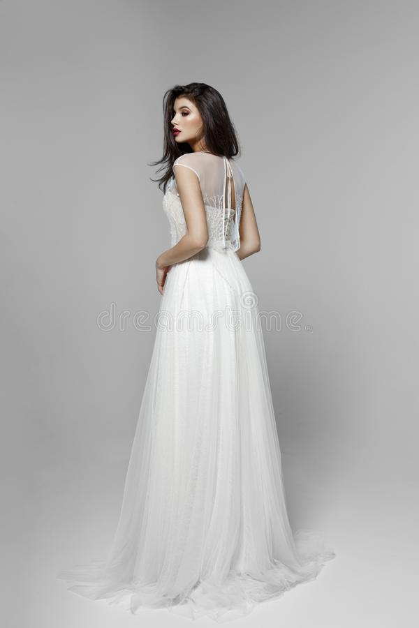 Взгляд со стороны нежной модели брюнета в классическом белом платье свадьбы, на белой предпосылке стоковые изображения rf