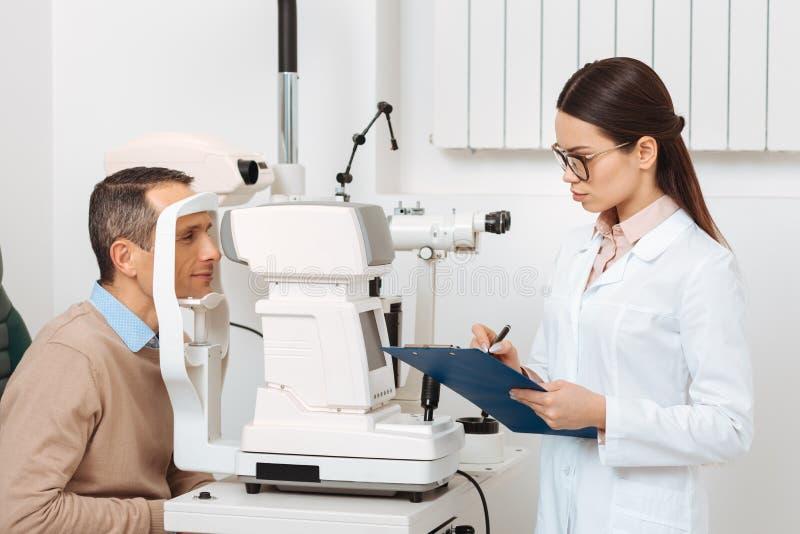 взгляд со стороны пациента получая рассмотрение глаза в разрезанной лампе стоковые фотографии rf