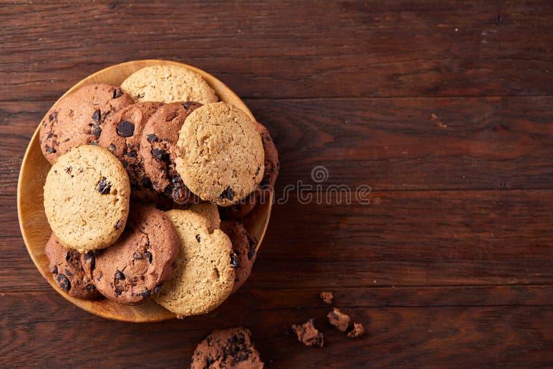 Взгляд со стороны печений обломока шоколада на деревянной плите над деревенской предпосылкой, селективным фокусом стоковое изображение