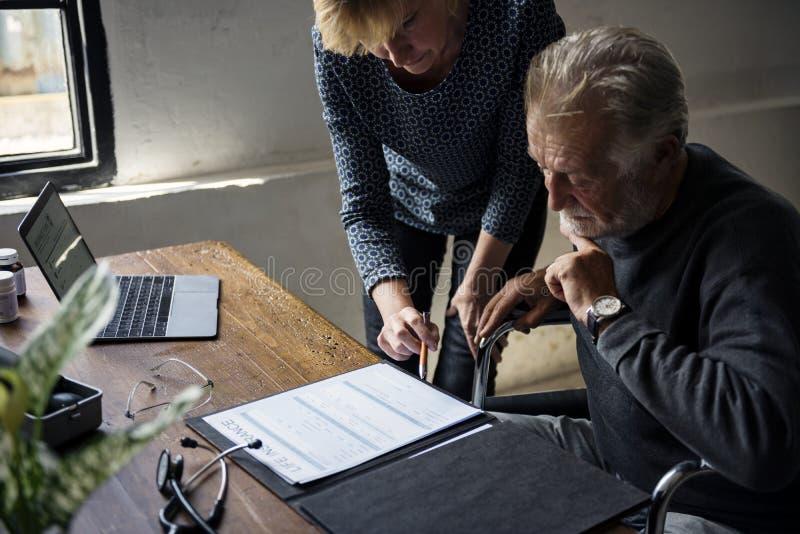 Взгляд со стороны пожилого человека сидя на кресло-коляске смотря форму контракта страхования жизни стоковое фото rf