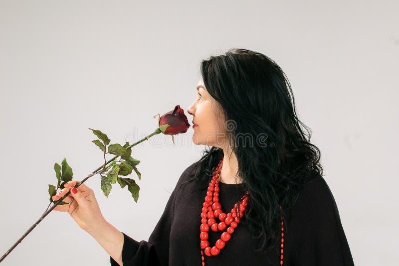 Взгляд со стороны польностью вычисляемой женщины в черном платье и этнической красной розе обнюхивать ожерелья на серой предпосыл стоковое изображение rf
