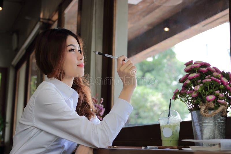 Взгляд со стороны привлекательной молодой азиатской бизнес-леди держа ручку и имеет идею в кафе кофе стоковые фотографии rf