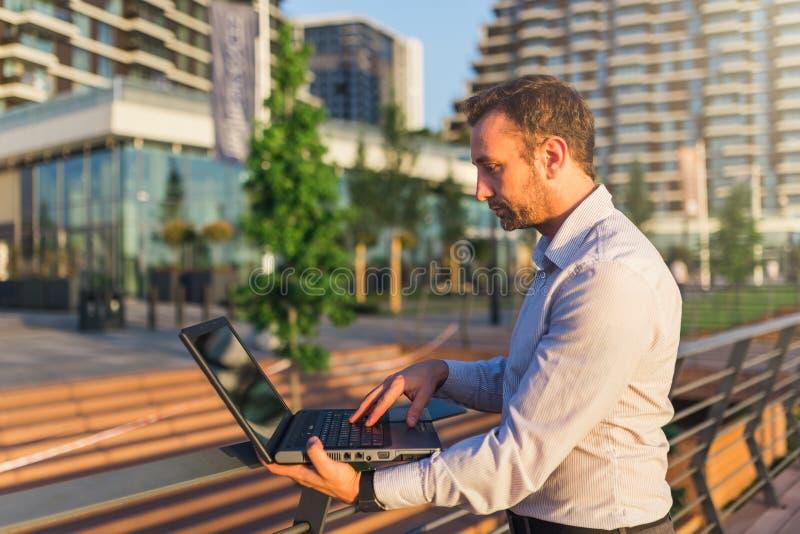 Взгляд со стороны профессионала дела с ноутбуком outdoors стоковое фото