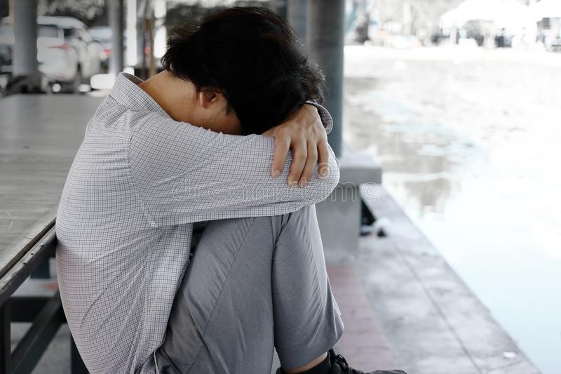 Взгляд со стороны разочарованного вымотанного молодого азиатского бизнесмена сидит и обнимает его колени до комода стоковые фото