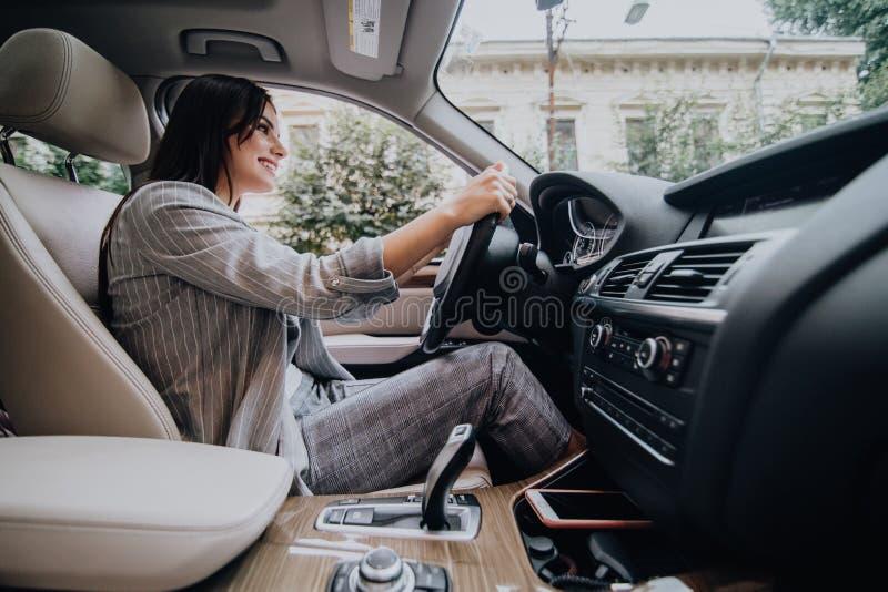 Взгляд со стороны разочарованной молодой бизнес-леди управляя автомобилем стоковое изображение rf
