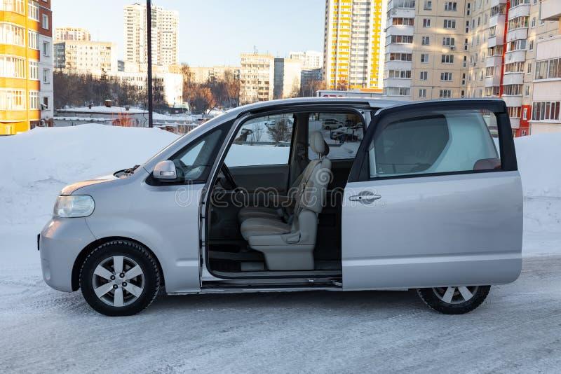 Взгляд со стороны семьи roomy автоматический бренда porte Тойота в сером цвете с раскрытой автоматической дверью снаружи в зиме,  стоковое изображение