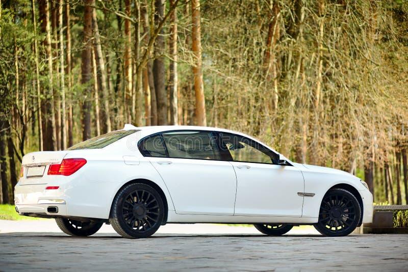 Взгляд со стороны современного роскошного автомобиля BMW 750Li XDrive трехчетвертной припаркованный на каменной вымощенной стоянк стоковые изображения