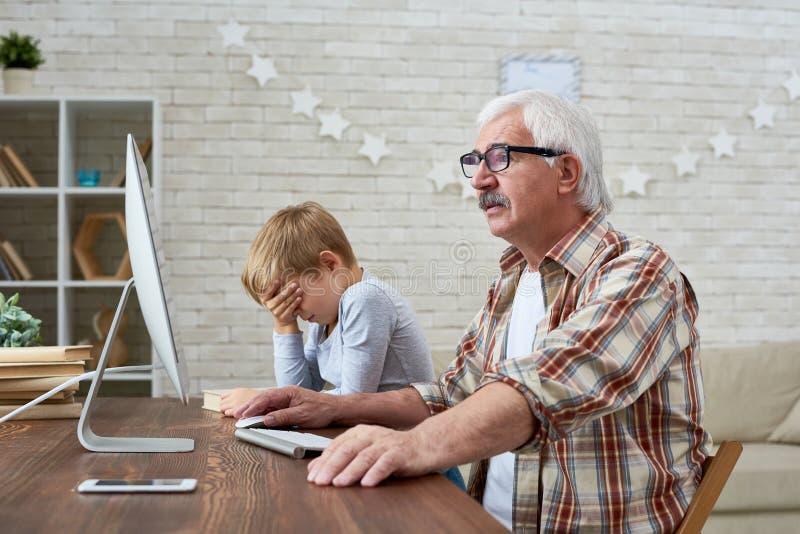 Взгляд со стороны старика используя ПК стоковое фото