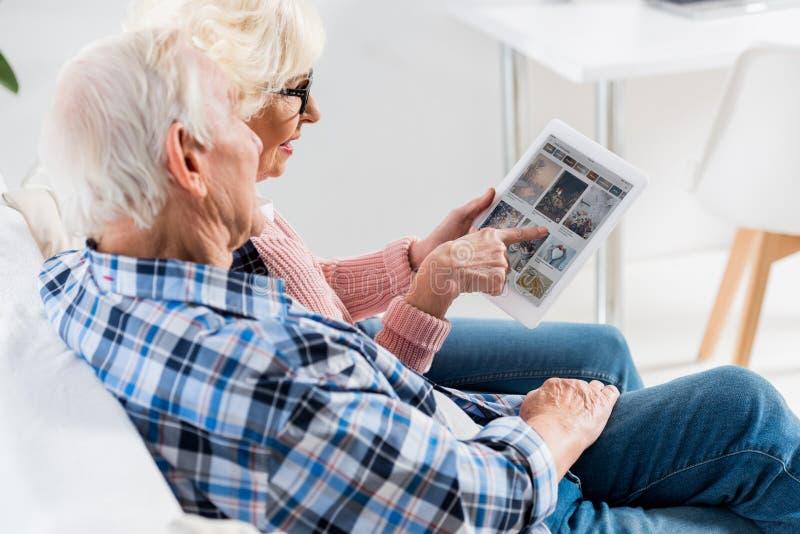 взгляд со стороны старших пар используя цифровую таблетку с pinterest стоковое фото