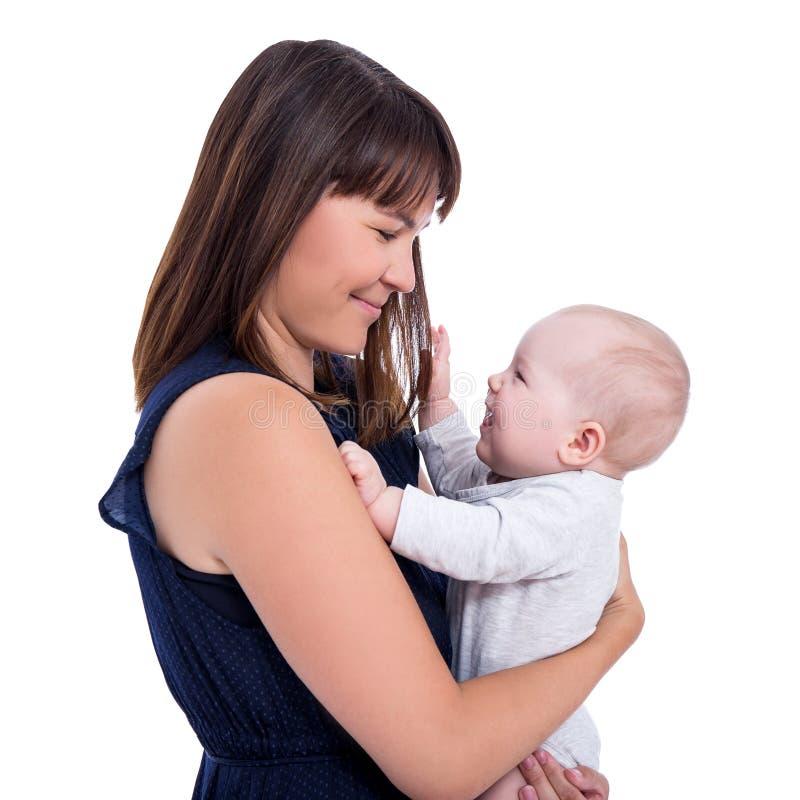 Взгляд со стороны счастливой красивой молодой матери держа маленького младенца стоковое фото