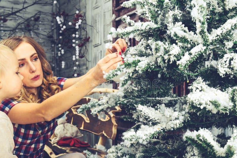 Взгляд со стороны счастливой мамы и ее сына украшая рождественскую елку на стоковое изображение