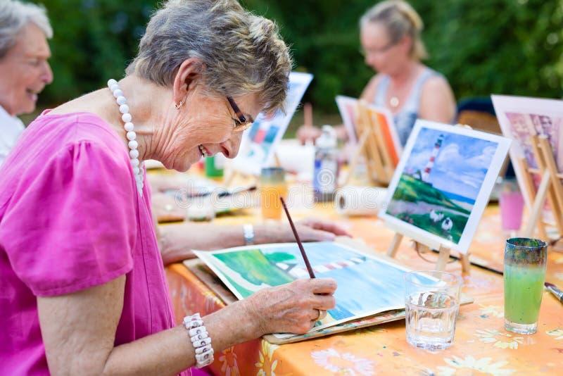 Взгляд со стороны счастливой старшей женщины усмехаясь пока рисующ как рекреационный outdoors деятельности или терапии вместе с г стоковое фото rf