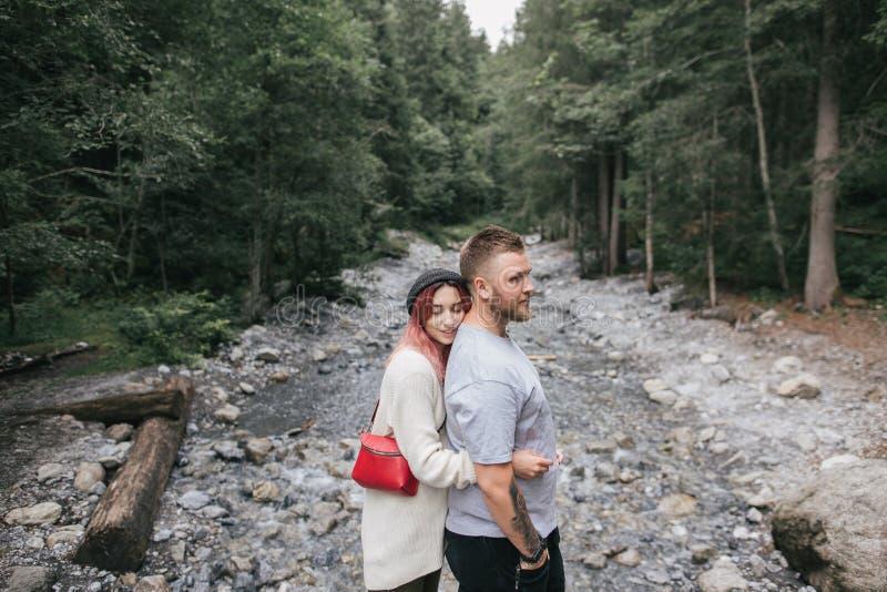 взгляд со стороны счастливых молодых пар в любов обнимая около быстрого реки горы стоковое фото rf