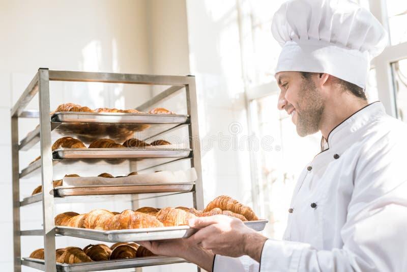 Взгляд со стороны усмехаясь хлебопека принимая поднос стоковые фотографии rf