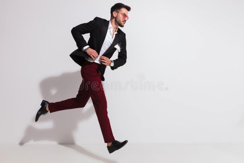 Взгляд со стороны элегантного человека бежать и застегивая его костюм стоковые изображения