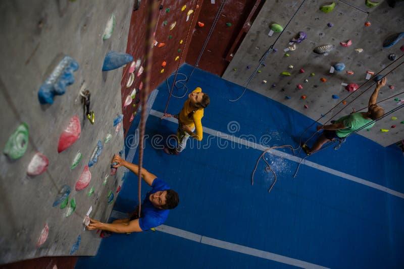 Взгляд спортсменов рассматривая взбираясь стену в оздоровительном клубе стоковые фотографии rf