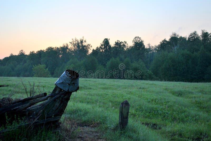 Взгляд старой загородки, зеленого луга и леса на восходе солнца стоковые фотографии rf