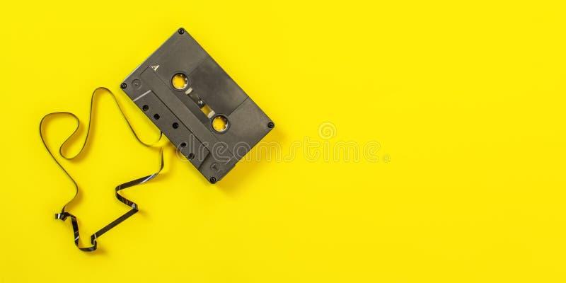 Взгляд столешницы, магнитофонная кассета с некоторой лентой вне на желтой предпосылке Широкий космос знамени для права текста стоковая фотография rf