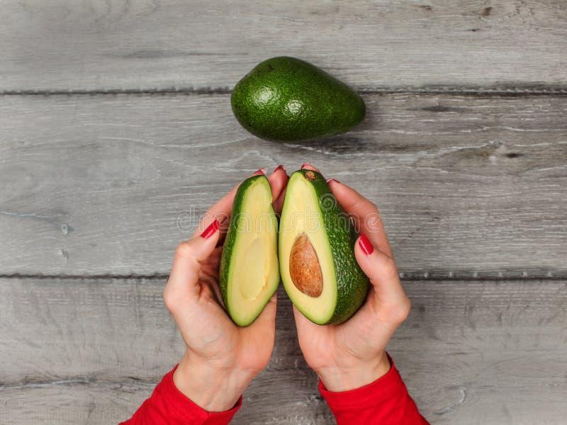 Взгляд столешницы, молодая женщина вручает держать 2 половины авокадоа c стоковое фото rf